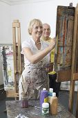 foto of middle class  - Two adult students painting at easel in art class - JPG