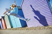 stock photo of herne bay beach  - Full length of young woman jumping in front of beach huts during summer - JPG