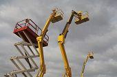 foto of cherry-picker  - Hydraulic lift machines against stormy sky - JPG