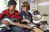 Happy multiethnic boys playing guitars in garage