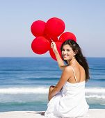 Beautiful girl with red ballons sitting in the beach