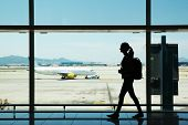 stock photo of board-walk  - Silhouette of young woman walking at airport - JPG