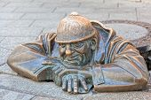 Cumil - statue of man peeking out from under a manhole cover