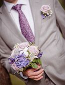 stock photo of fiance  - closeup of a fiance in suit with wedding flowers  - JPG