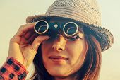 stock photo of binoculars  - Young traveler woman in hat looks through binoculars - JPG