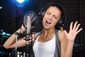foto of recording studio  - Portrait of young woman recording a song in a professional studio - JPG