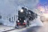 stock photo of train-wheel  - Retro steam train departs from the railway station at sunset - JPG
