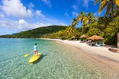 pic of paddling  - Active young woman on tropical beach vacation paddling on stand up board - JPG