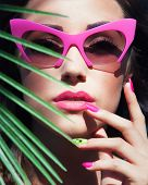 image of nail-art  - Face close up of young beautiful woman under a palm tree wearing sunglasses - JPG