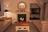 picture of cozy hearth  - A luxurious modern living room with comfortable couches and a lit fire - JPG