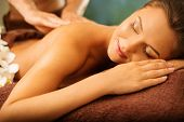 pic of massage oil  - Beautiful young woman having massage in a spa salon - JPG