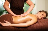 picture of massage oil  - Beautiful young woman having massage in a spa salon - JPG