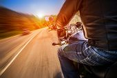 picture of biker  - Biker driving a motorcycle rides along the asphalt road - JPG