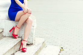 pic of stiletto  - beautiful long  legs girl in red shoes in blue dress sits in the city - JPG