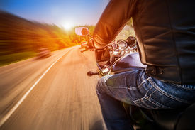 image of biker  - Biker driving a motorcycle rides along the asphalt road - JPG