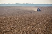 stock photo of potato-field  - The tractor harvester working on the field - JPG