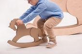 stock photo of horse girl  - Selective focus on the little lovely girl wearing blue shirt and brown pants playing with the little wooden toy horse - JPG