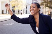 image of hail  - a young business woman hailing a taxi - JPG