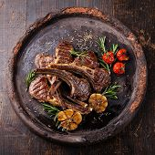 stock photo of lamb  - Roasted lamb ribs with spices and garlic on dark textural background - JPG