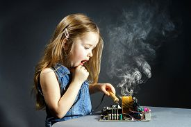 image of hooligan  - Cute little girl helping father to repair old computer motherboard using solderer - JPG