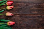 image of bittersweet  - Red tulips flowers bouquet on old wooden table background - JPG