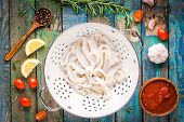 stock photo of squid  - fresh raw squid rings in a colander on a wooden table with tomatoes lemon rosemary garlic - JPG