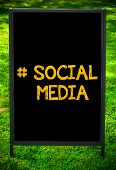 stock photo of hashtag  - Hashtag Social Media message on sidewalk blackboard sign against green grass background - JPG
