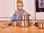 pic of pinafore  - Child holdig group pan at kitchen - JPG