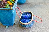 image of planters  - Woven basket with blue wool and yarn next to a large ceramic planter with flowers
