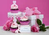 pic of cake stand  - Happy Mothers Day pink and white cupcakes on retro style cake stands and large gift box on vintage white wood table - JPG