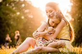stock photo of caress  - Mother is cuddling her worried child outdoor in nature - JPG