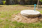 stock photo of cylinder  - underground cement cylinder of lavatory cesspit in lawn yard - JPG