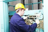 pic of adjustable-spanner  - Male technician machinist worker at work adjusting elevator mechanism of lift with spanner - JPG