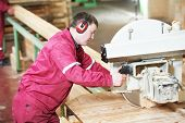 pic of sawing  - Closeup process of carpenter worker with circular saw machine at wood beam cross cutting during furniture manufacture - JPG