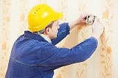 picture of electric socket  - electrician worker at electric wall outlet or light switch socket installation work - JPG