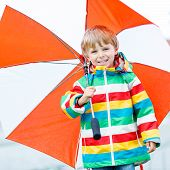 pic of rainy day  - Little blond kid boy walking with big umbrella outdoors on rainy day - JPG
