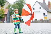 foto of rainy day  - Preschool boy in waterproof clothes and boots walking on the street of a small town on rainy day - JPG
