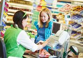 stock photo of supermarket  - Customer buying food at supermarket and making check out with cashdesk worker in store - JPG