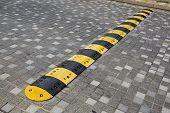 picture of bump  - Traffic safety speed bump on an asphalt road - JPG