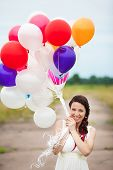 picture of latex woman  - Happy young woman holding in hands colorful latex balloons outdoors - JPG