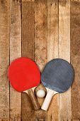 foto of ping pong  - Ping pong paddles and ball on vintage wooden background - JPG