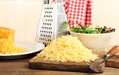 stock photo of grating  - Grated cheese on wooden table in kitchen - JPG