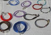 stock photo of flea  - A lot of colorful bracelets for sale at flea market - JPG