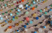 stock photo of flea  - many valuable necklaces in gold and gemstones for sale at flea market - JPG