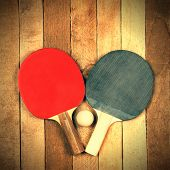stock photo of ping pong  - Ping pong paddles and ball on vintage wooden background - JPG