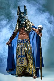picture of pharaohs  - The man in the image of the ancient Egyptian Pharaoh  with a  mask of  Anubis on his face on blue background - JPG