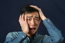 foto of disappointed  - Disappointed young Asian man crying and looking sideways - JPG