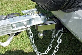 stock photo of ball chain  - A trailer is secured to the back of a powerful vehicle to be towed to its destination for unloading - JPG