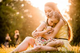 foto of cuddle  - Mother is cuddling her worried child outdoor in nature - JPG