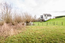 pic of hamlet  - In the floodplain of the river near a hamlet in the Netherlands the water is almost at the base of the dike - JPG